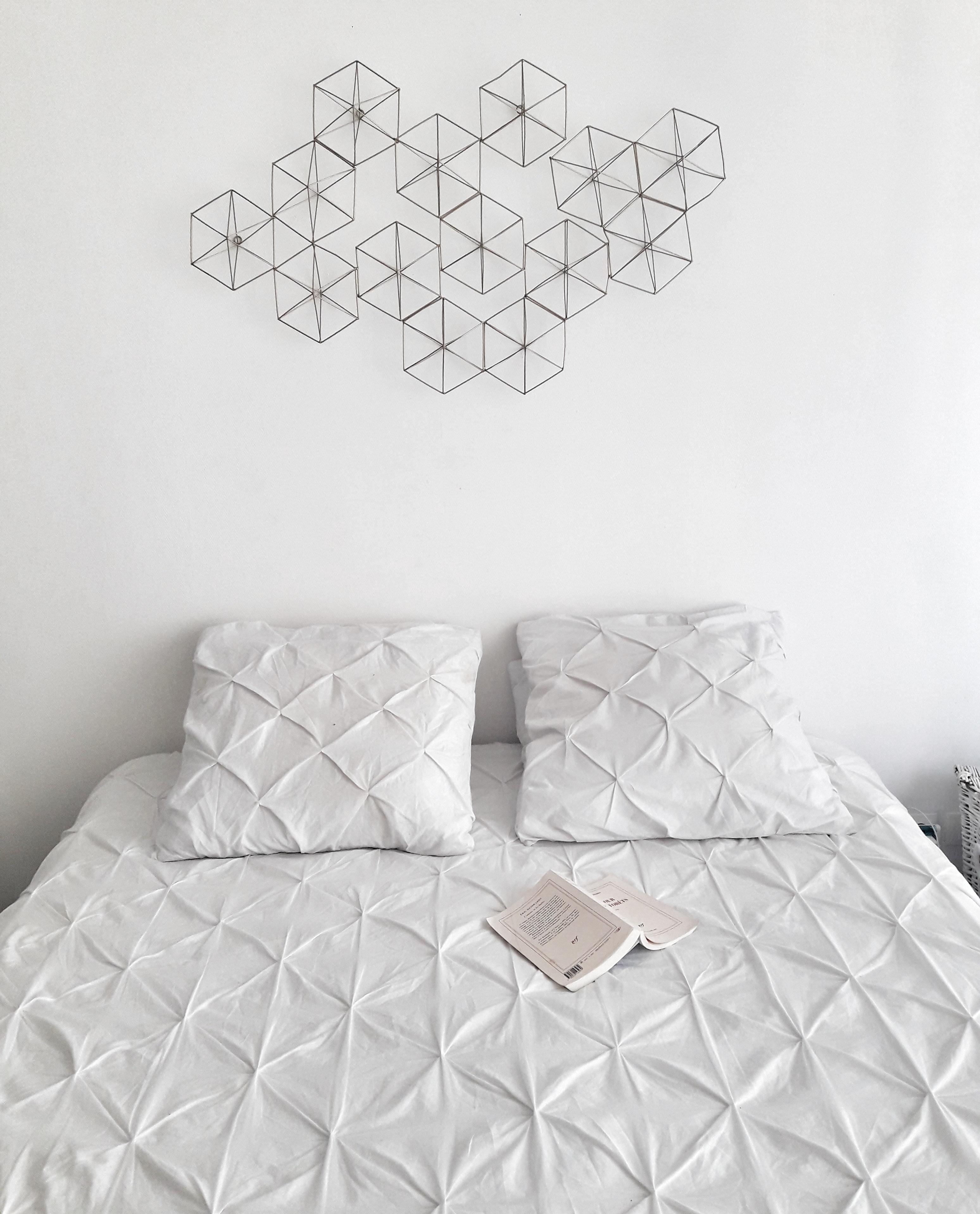 Je voulais quelque chose de simple. les draps sont blancs j'ai trouvé du linge de lit géométrique se mariaent parfaitement avec une décoration murale or que j'avais chiné chez maison du monde. On ne voit pas mais le lustre est dans le même thème. J'ai choisi un lit sans tête de lit et surtout avec des rangements, ultra utile (6 tiroirs!)